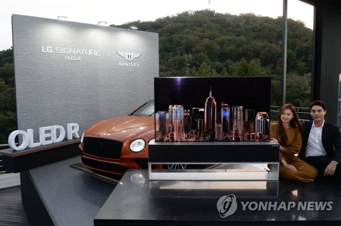 This photo provided by LG Electronics Inc. on Oct. 14, 2020, shows models promoting the company's rollable TV, the Signature R, with a Bentley Continental GT at an event for VVIP (very very important person) consumers at a Seoul hotel. (PHOTO NOT FOR SALE) (Yonhap)